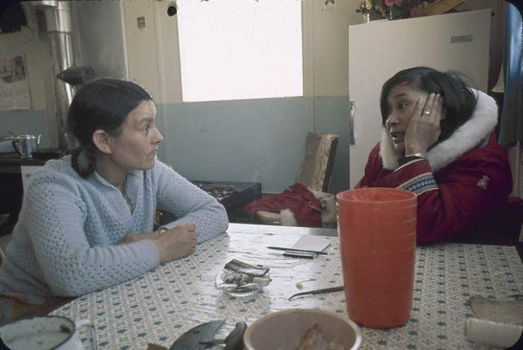 Two women talking at a kitchen table [Eunice Koonoo Arreak (left) and Sophie Qaunak (right)]